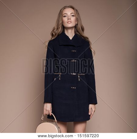 studio fashion portrait of yong pretty blonde woman in coat on beige background.