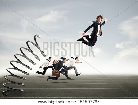 Businessman jumping on a spring during a race with opponents