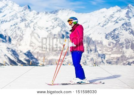 Young active woman skiing in mountains. Female skier kid with safety helmet goggles and poles enjoying sunny winter day in Swiss Alps. Ski race for adults. Winter and snow sport in alpine resort.