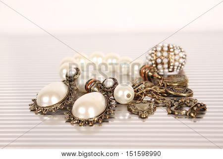 Close-up of rings, earrings and bracelet. Set of jewelery with pearls