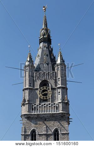 Ancient Bell Tower - watchtower - Ghent Belfort (Belfry) - top close-up on blue sky background