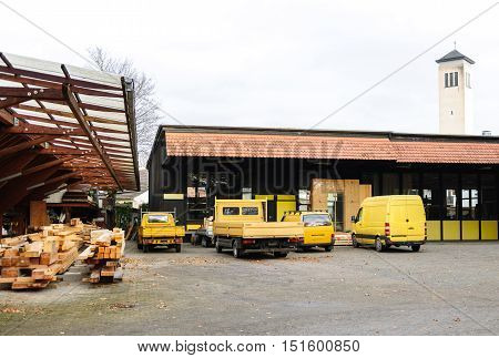 Factory company fleet of generic commercial lorries and vans parked in a row ready for cargo distribution of wooden manufactured products