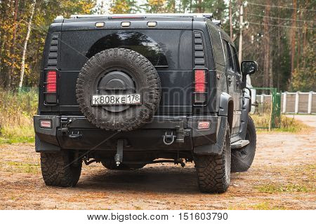 Saint-Petersburg Russia - October 9 2016: Black Hummer H2 vehicle stands on dirty country road in Russian countryside rear view