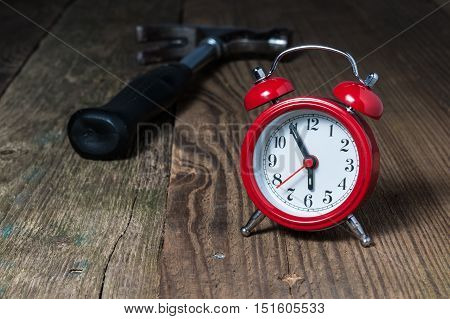 Red alarm clock at five minutes to six oclock and hammer in the background on the wooden table