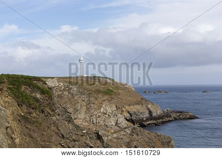 Cliff By The Coast Over The Sea With Lighthouse
