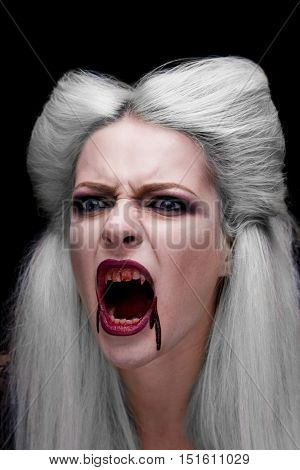 Beautiful blonde girl vampire is screaming. The blood is on the mouth. Halloween look.