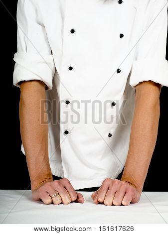 Professional chef leaning firmly onto a table with white cover