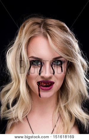 Beautiful blonde girl vampire. The blood is on the mouth and eyes.
