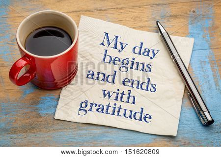My day begins and ends with gratitude - positive affirmation words - handwriting on a napkin with a cup of coffee