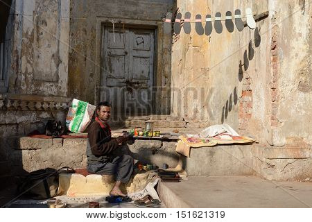 AHMADABAD GUJARAT INDIA - JANUARY 26: Shoemaker fixing shoes in streets of Indian cities in the Gujarat state in India Ahmadabad in January 28 2015
