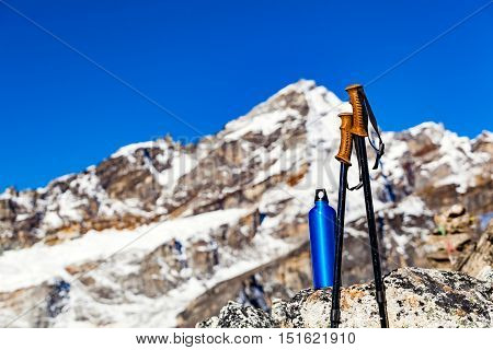Hiking Gear over Himalaya Mountains Background. Trekking Stick and Water Bottle in Inspirational High Himalayas Landscape over Blue Sky in Nepal.