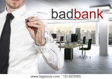 businessman with necktie writing badbank in the air modern office