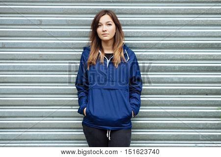 Stylish Sporty Brunette Woman Hands In Pockets In Trendy Urban Outwear Posing At City Park On Cold R