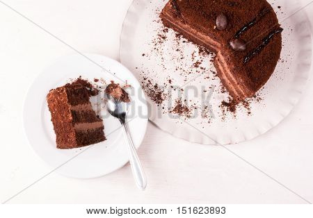 Chocolate cake with cream on a white wooden table. One piece of cake is on the plate, girl eats it, hand in the picture, top view, copy space
