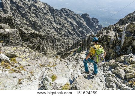 Two hikers in helmets descends a rocky gully.