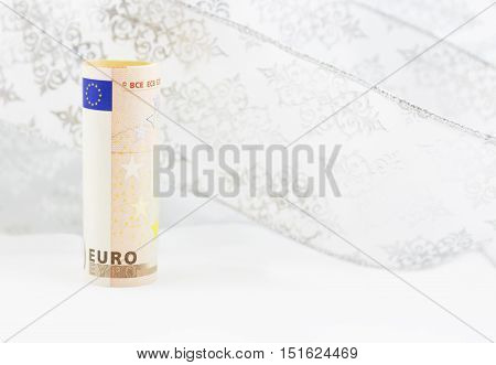 Euro currency on swirl of white snowflake ribbon background reflects shifting financial environment