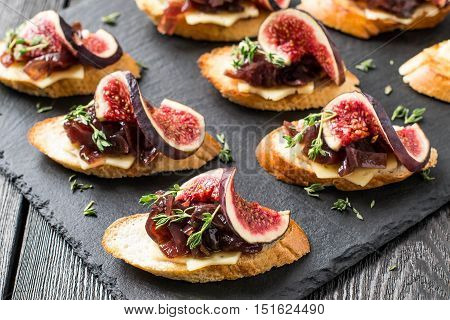 Canape or crostini with toasted baguette cheese onion jam figs and fresh thyme on a slate board. Delicious appetizer ideal as an aperitif. Selective focus