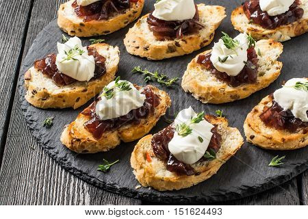 Canape or crostini on slate board. Ideal as an aperitif. Ingredients: toasted baguette with sunflower and flax seeds onion jam cream cheese and fresh thyme