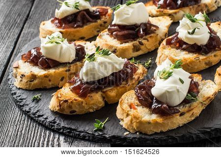 Canape or crostini on slate board. Ideal as an aperitif. Ingredients: toasted baguette with sunflower and flax seeds onion jam cream cheese and fresh thyme. Selective focus
