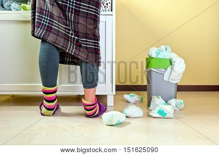 Woman in plaid skirt wearing blue tights and colourful socks changing babies diapers some used ones placed in a waste bucket and others around it on the floor.