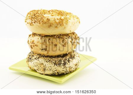 Three bagels stacked on green plate. Copy space on white background. Types are garlic onion and everything.