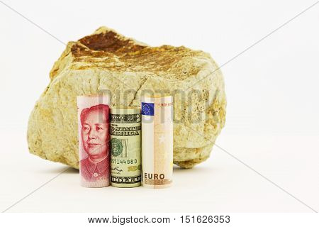 Influential currencies the Chinese yuan American dollar and European Union euro placed next to rock reflect rocky worldwide financial times.