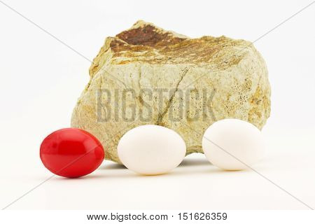 Investment problems reflected in red egg placed with ordinary eggs in rocky trying times. Rock with crack reflects danger and difficulty.