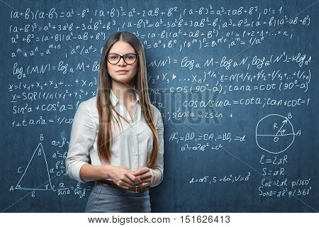 Young businesswoman with glasses standing on the background of blackboard with mathematical formulas. Learning and teaching. Algebra and geometry. School and education.