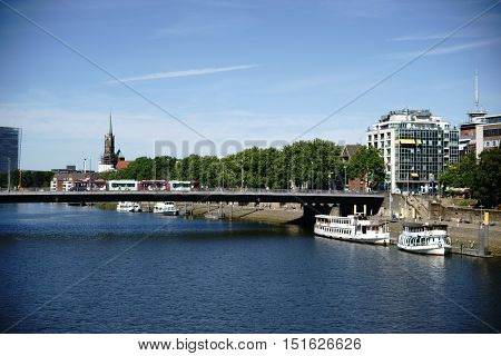 The view over the river Weser and the city of Bremen with buildings and infrastructure.