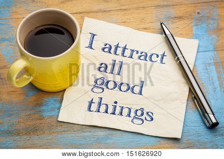 I attract all good things - positive affirmation  words - handwriting on a napkin with a cup of coffee