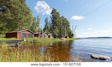Group of red boathouse by the waterside pine trees and blue sky in the background