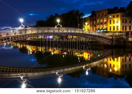 Night view of famous illuminated Ha Penny Bridge in Dublin Ireland with reflection in the river