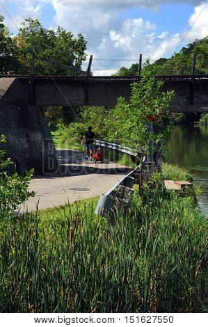 Man pulls child and wagon through the underpass of a train track bridge in Stoughton Wisconsin. Road runs alongside the Yahara River.