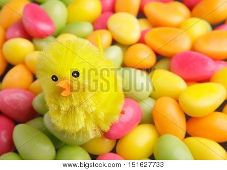 A chicken decorate pile of Easter candy in the shape of eggs in several colors.