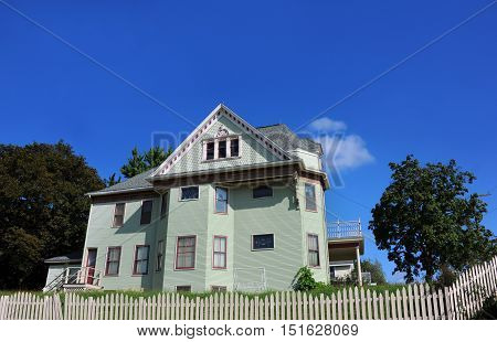 Beautiful pastel green and red painted house has Victorian architecture. White wooden fence surrounds property.