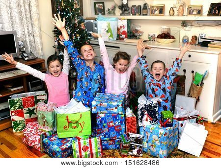 Four small siblings celebrate their joy on Christmas morning by yelling and shouting happily. They are sitting in front of the Christmas tree in their home.