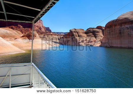 This houseboat has a view! Beautiful sandstone rocks and steep cliffs tower over Lake Powell and its waterway.