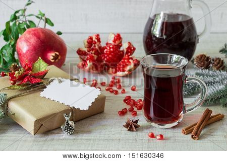 Cap of pomegranate juice or cocktail, ripe pomegranate, slices, seeds, cinnamon, star anise, jug, fir branches, present on light white wood background. Pomegranate juice cocktail, pomegranates, gift