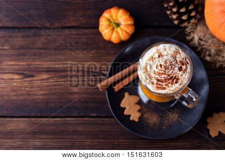 Pumpkin smoothie, spice latte. Boozy cocktail with whipped cream on top on a wooden background. Copy space Top view