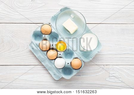 View from above on brown and white eggs, milk and butter over white wooden table