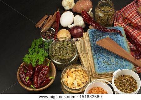 Cookbook and spices on wooden table. Cookbook and ingredients. Garlic, chili peppers and onion. Ingredients for cooking. Home Kitchen.