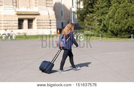 Young woman with suitcase in the city