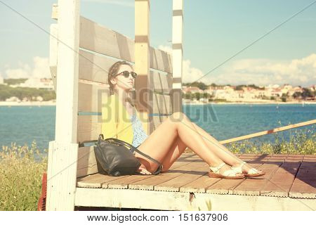 Young Girl Relaxing by the Sea. Summer Vacation Daydream. Retro Toned Photo.