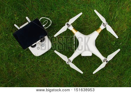 White Quadrocopter With Remote Control On Grass, Close-up. New U