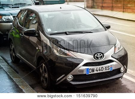 STRASBOURG FRANCE - MAR 15 2016: Toyota Aygo two door car parked in urban enviroment on a rainy day