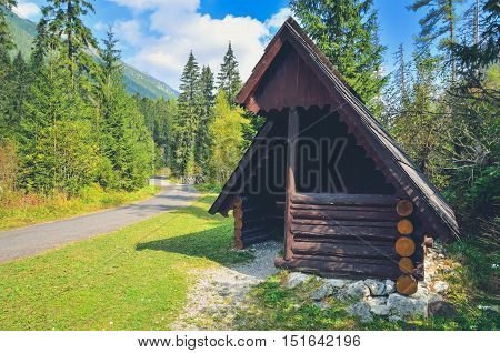 Summer mountain landscape. Wooden hut and asphalt road in the mountains on a sunny day.