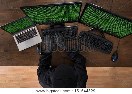 High Angle View Of Robber Hacking Computers And Laptop In Office