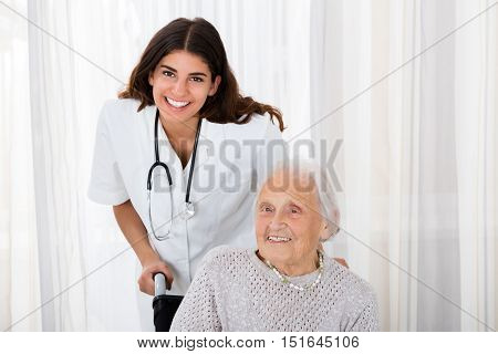 Portrait Of Happy Female Doctor With Handicapped Senior Patient In Hospital