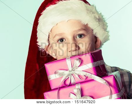 Happy childhood holiday christmas time.. Little boy child in red santa helper hat holding stack of pink presents gift boxes on blue