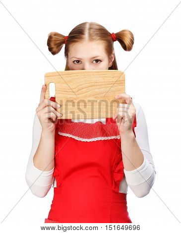 Young beautiful housewife in bright red apron with funny tails looking over wooden cutting board isolated on white background. Copy space.